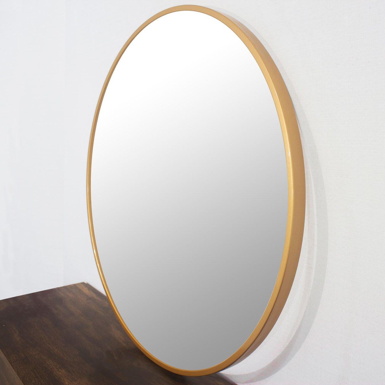 Foto lateral, espelho redondo com moldura dourada.