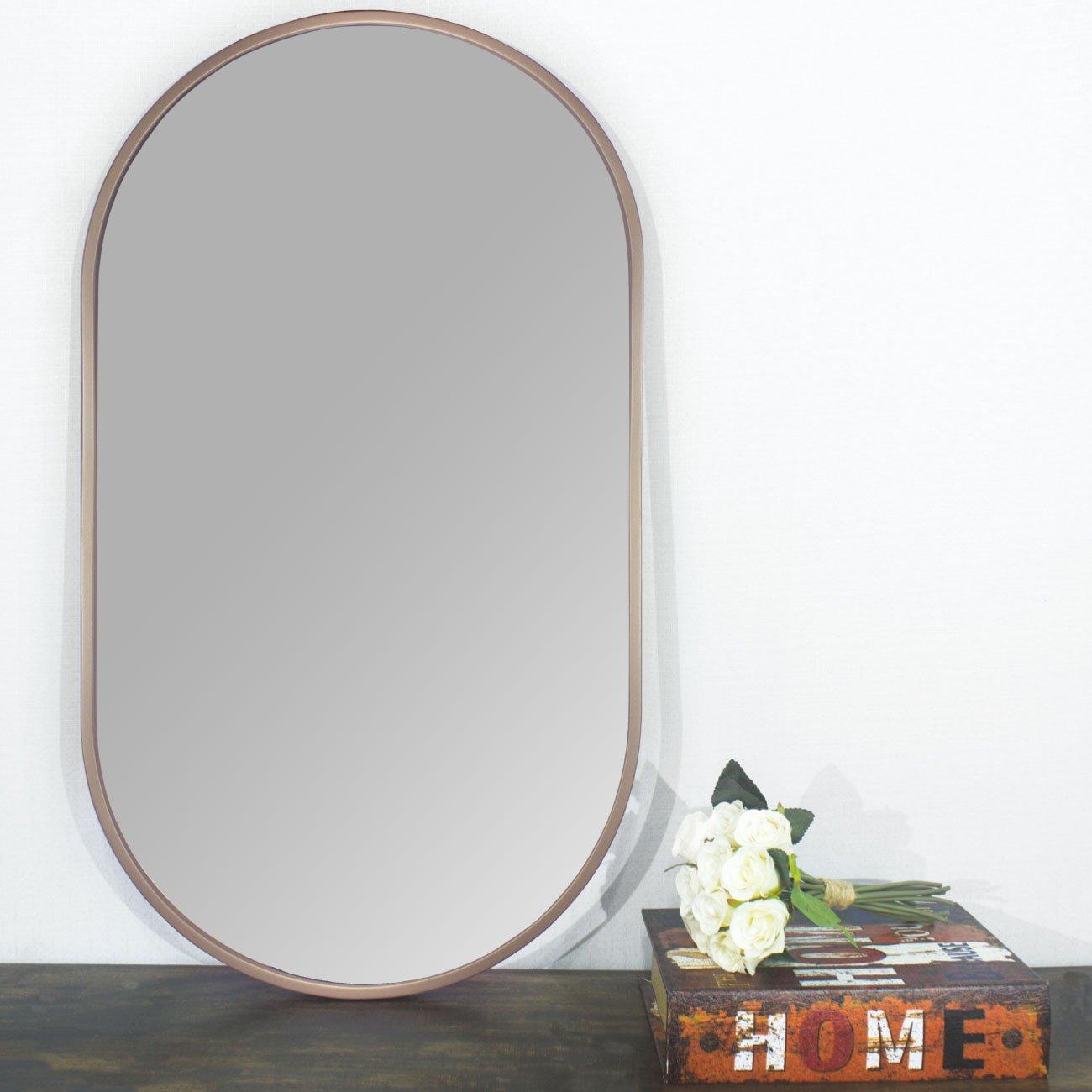 Espelho retangular cobre sobre aparador.