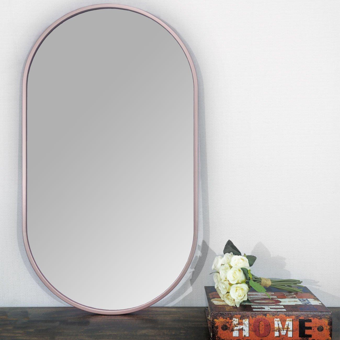 Espelho retangular cobre rosê gold sobre aparador.