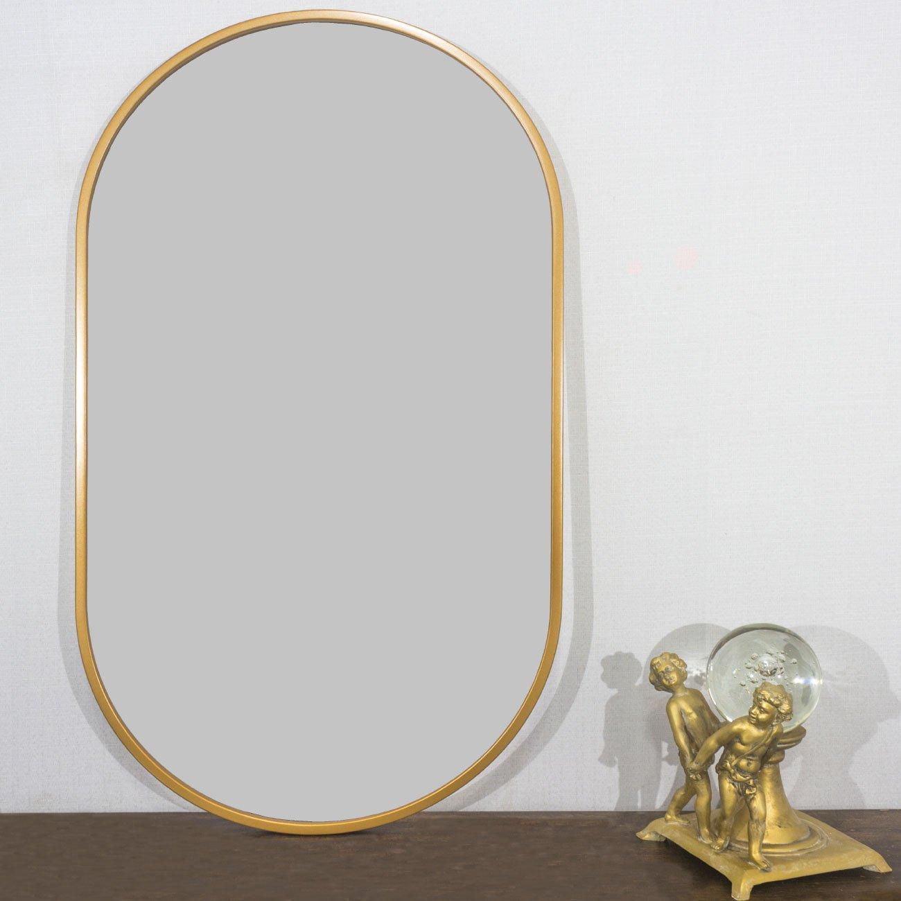 Espelho retangular dourado sobre aparador.