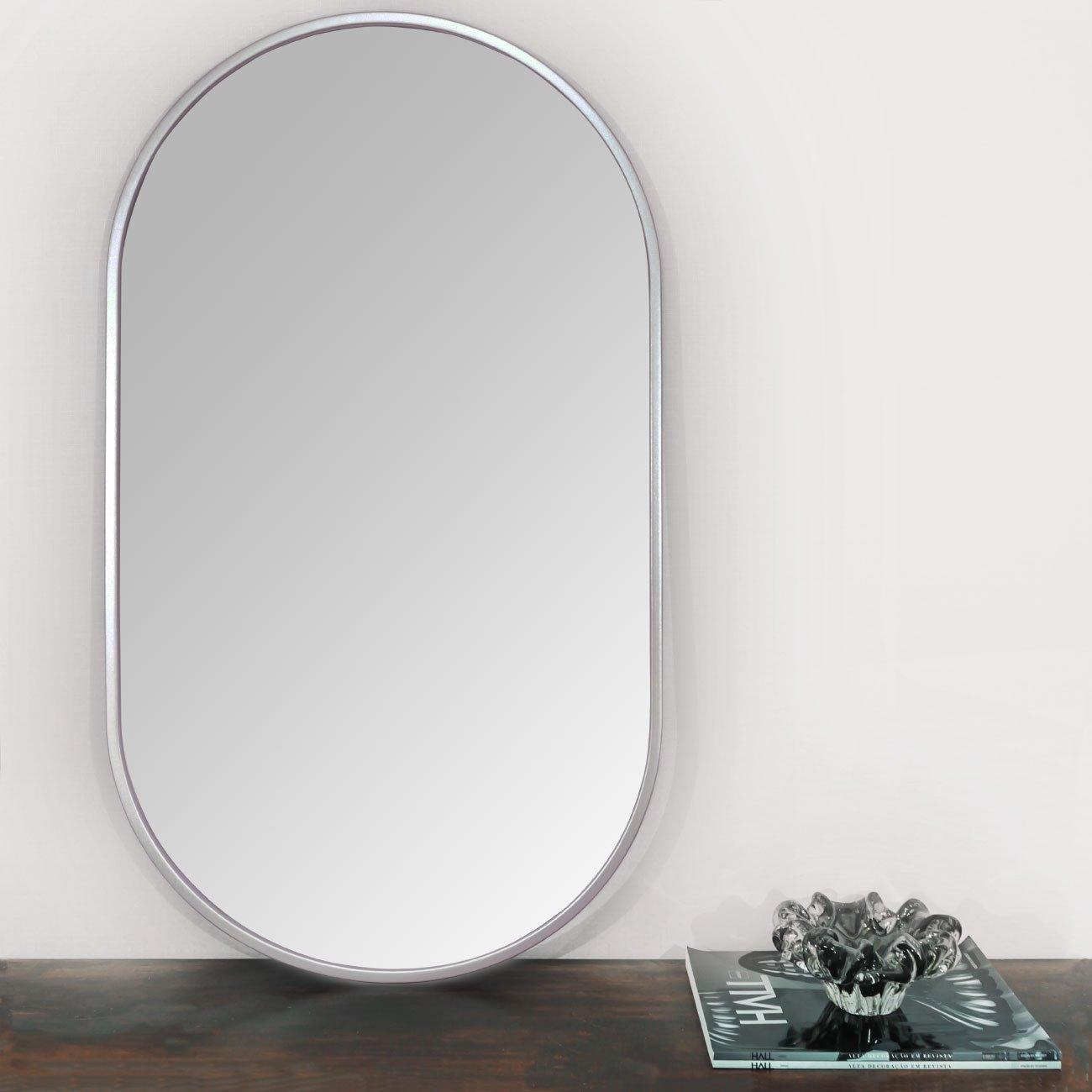 Espelho retangular prata sobre aparador.