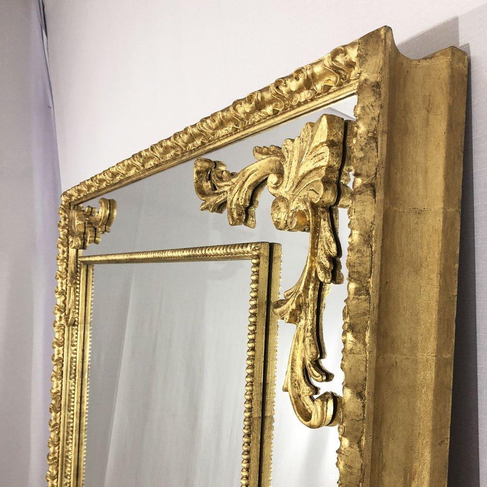 Espelho decorativo dourado com moldura gravadaeapliques sobre o espelho.